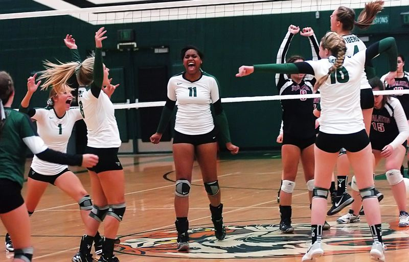 by: DAN BROOD - CELEBRATION TIME -- Members of the Tigard High School volleyball team, including junior Sasha Hershey (11), break into celebration after scoring the final point in their 25-14, 25-18, 25-19 win over Tualatin in Tuesday's match at Tigard.