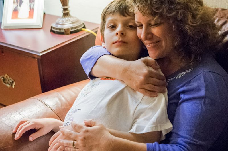 by: HILLSBORO TRIBUNE PHOTO: CHASE ALLGOOD - Tobi Rates, executive director of the Autism Society of Oregon, cuddles with her 9-year-old son, Jacob, in their southeast Portland home. Rates believes Washington Countys Help Me Home program could be taken statewide.