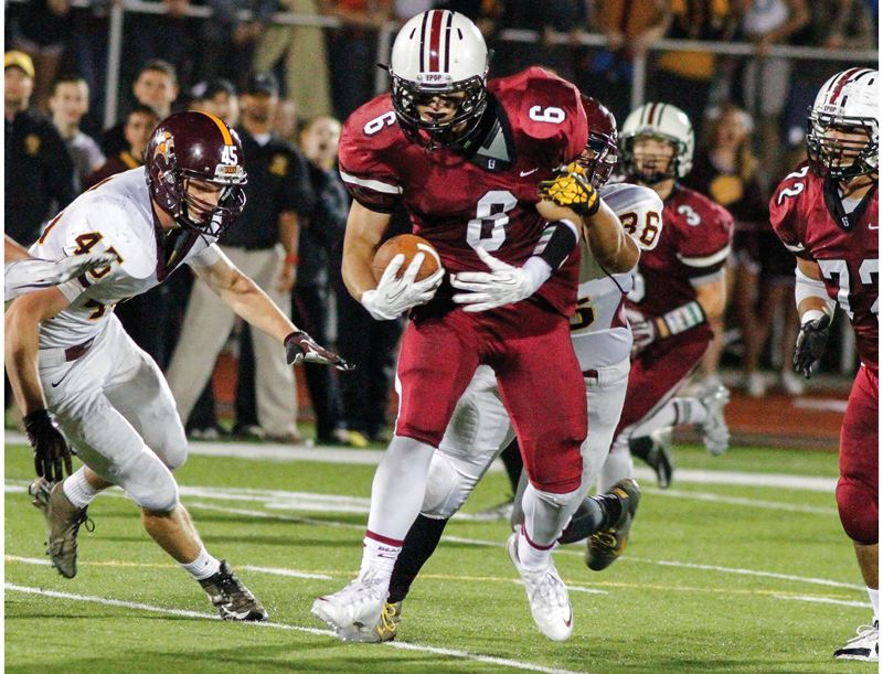 by: HILLSBORO TRIBUNE PHOTO: CHASE ALLGOOD - Glencoe senior Kyle Campbell drags a Forest Grove defender for extra yardage during last Friday's 19-12 victory at Hare Field.
