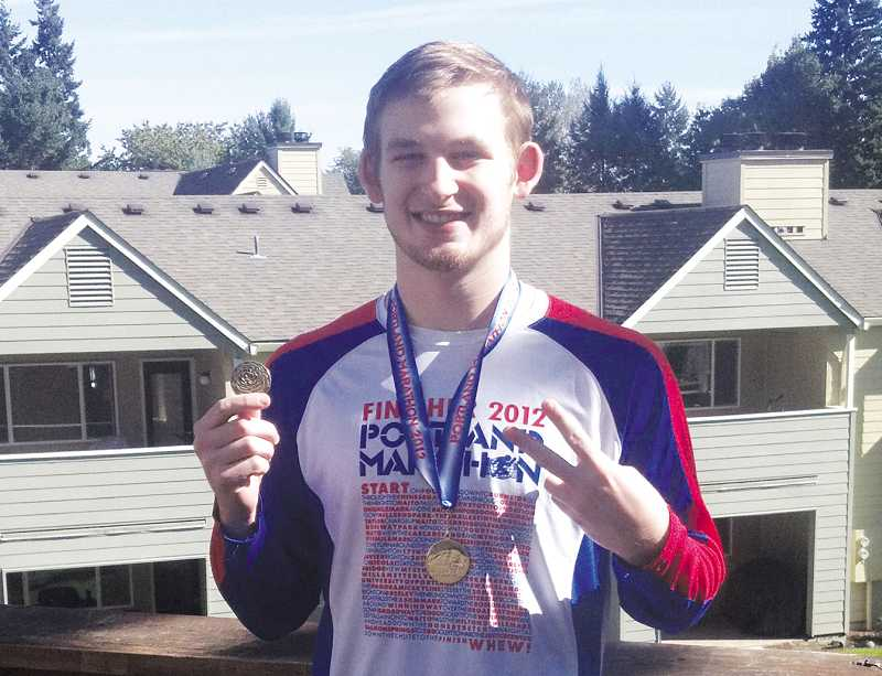 by: COURTESY PHOTO - Curtis Porter, the son of Jill Porter, wears his 2012 Portland Marathon shirt and showcases his medal. The Porters compete in the event to support Thelma's Place, a Canby nonprofit.