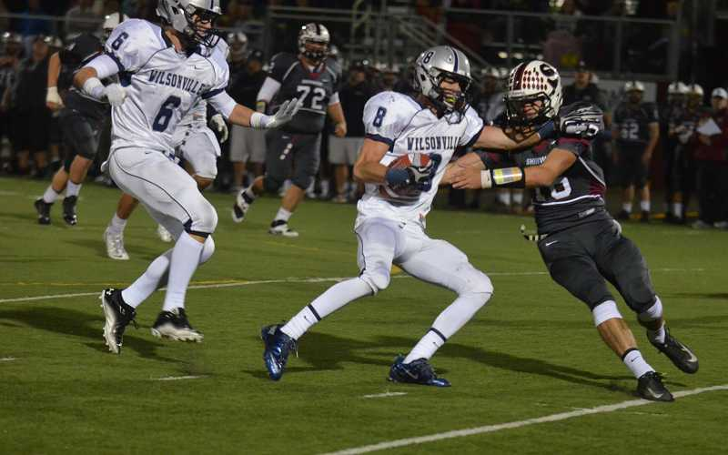 by: JEFF GOODMAN - Wilsonville senior Tyler Carskadon (8) tries to fend of Sherwood quarterback Kevin Larkin after intercepting Larkin's pass late in the first half Oct. 11 at Contreras Memorial Stadium.