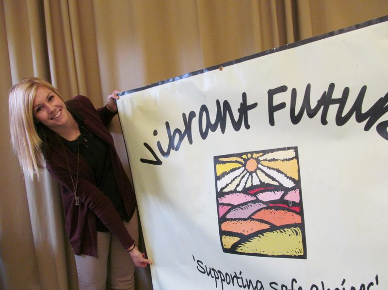 by: PHOTO BY ELLEN SPITALERI - Tracy Hoffman, coalition director of the Vibrant Futures Coalition, rolls out the Vibrant Future's banner at Northwest Family Services.