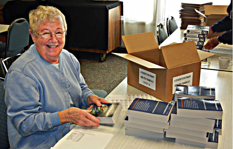 by: CONTRIBUTED PHOTO: GRESHAM ELKS - Liz Jones helps organize dictionaries given to 11 local elementary schools this fall by Gresham Elks.