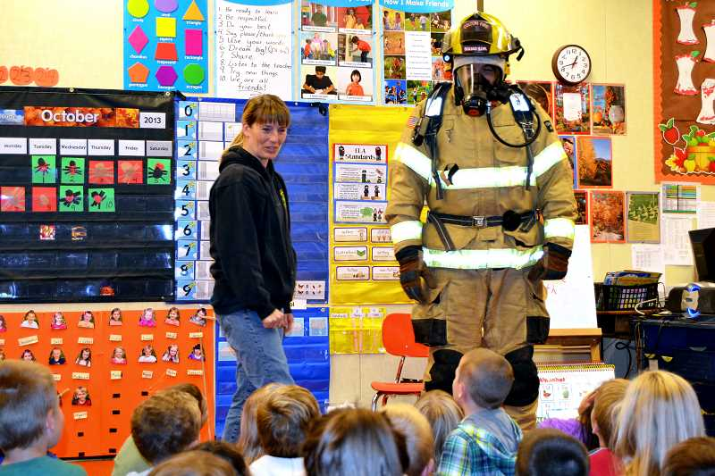 by: CINDY FAMA - Kindergarteners get a lesson in fire safety from Woodburn and Colton firefighters.