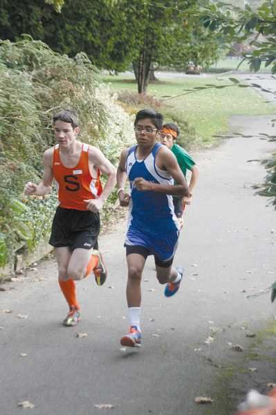 by: PHIL HAWKINS - Woodburn freshman Gustavo Lopez (right) paces a trio of runners at Bush Pasture Park Friday. Lopez finished the race with the fourth-fastest time and has been one of the Bulldogs best young cross country members this season.