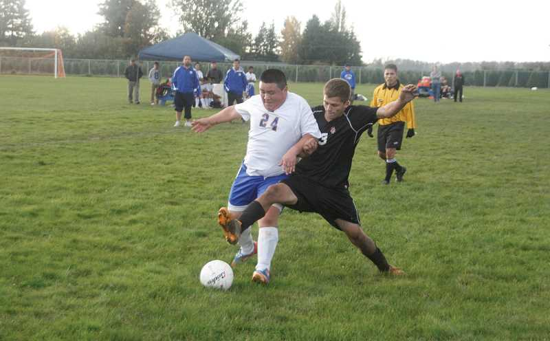 by: PHIL HAWKINS - Gervais midfielder Eliceo Leal (left) fights for the ball deep in Santiam Christian territory toward the end of the Cougars 7-0 victory over the visiting Eagles Oct. 8. Gervais is currently third in the district standings and on the cusp of their first trip to the playoffs since 2008.