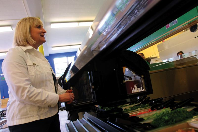 by: PAMPLIN MEDIA GROUP: JONATHAN HOUSE - Portland Public Schools nutrition director Gitta Grether-Sweeney checks out the healthy offerings at Oliver Lent Elementary School.