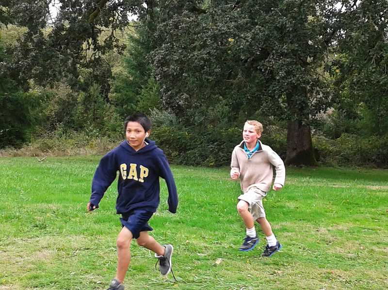 by: ISABEL GAUTSCHI - The students earned money for class activities and field trips for each lap they ran. Pictured: Raymond Garcia and Jed Shaver.
