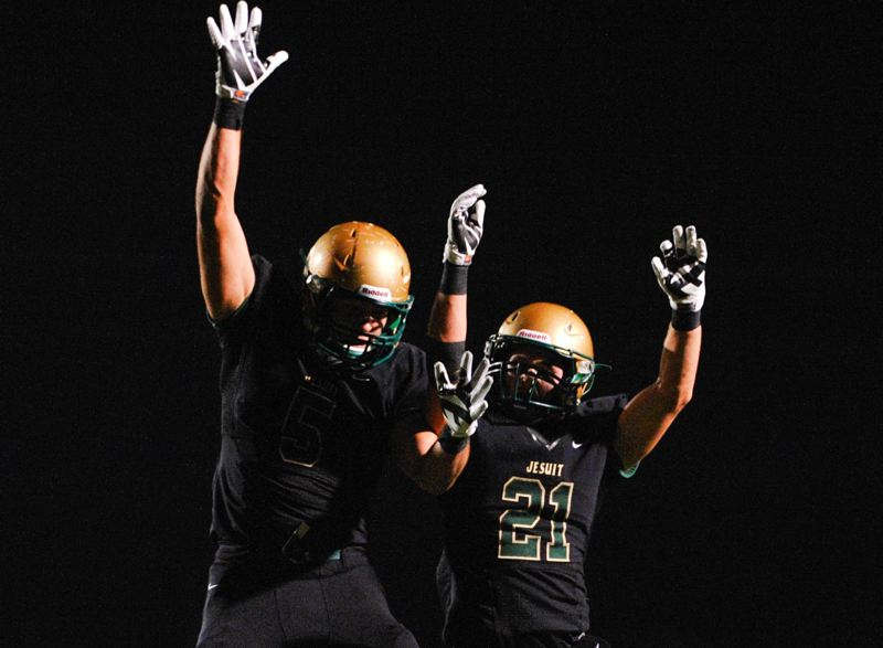by: TIMES PHOTO: JOHN LARIVIERE - Jesuit wide receiver Trent Werner (right) celebrates his late first quarter diving catch touchdown with Christian Martinek (left).