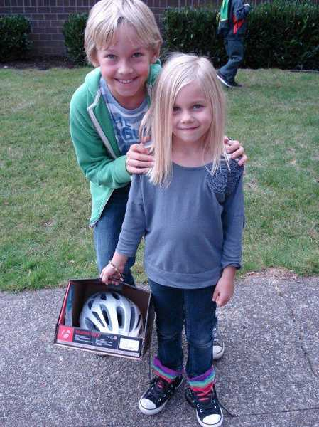 by: SUBMITTED PHOTO - Westridge first-grader Jane Evertons brother, fourth-grader Will Everton, hugs her after she learns she won her schools raffle for a bike helmet.