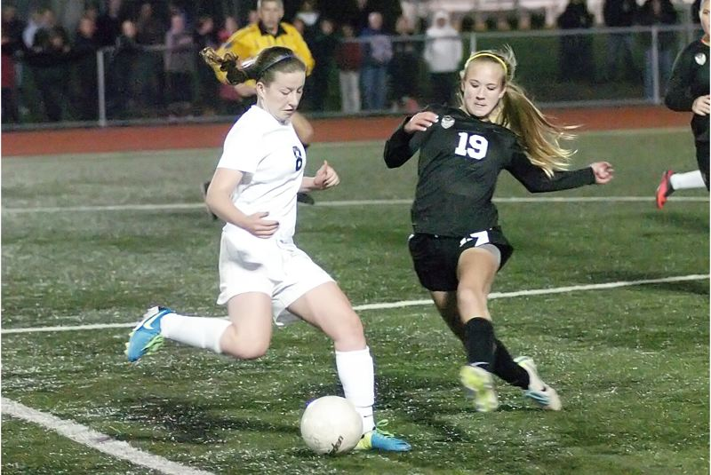 by: DAN BROOD - COLLISION COURSE -- Tigard sophomore Ellie Freeman (left) and Tualatin freshman Anna Verloo converge on the ball during Monday's match at Tigard High School. The teams played to a 1-1 tie.