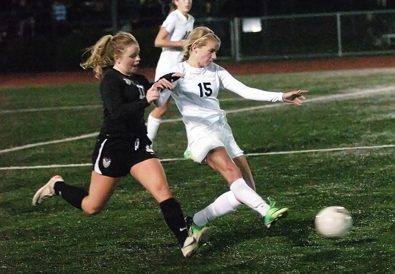 by: DAN BROOD - CLASH OF THE TITANS -- Tualatin junior Kyla Hackelman (left) and Tigard sophomore Natalie Bryant keep the pace quick during Monday's showdown.