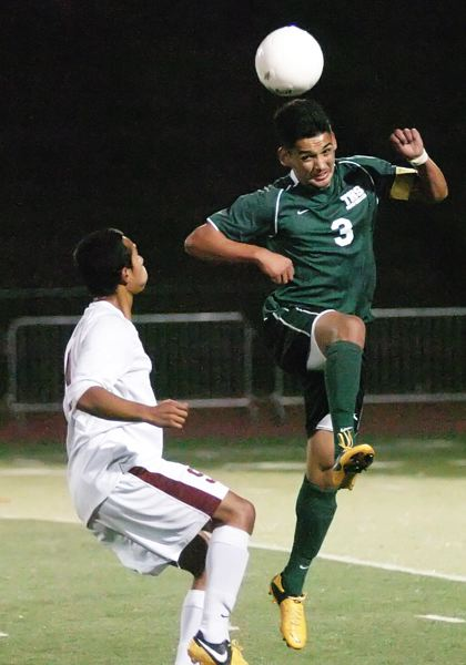 by: DAN BROOD - USING HIS HEAD -- Tigard senior Javier Sanchez-Figueroa (right) heads the ball as he goes up next to Tualatin junior Javier Miranda.