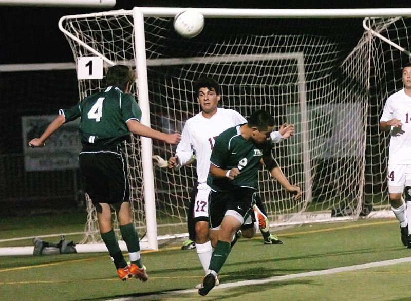 by: DAN BROOD - HEADS UP -- Tigard High School junior Jake O'Brien (4) heads the ball toward the Tualatin goal as Timberwolf junior Luis Martinez (17) approches during Monday's match at Tualatins.