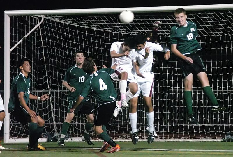 by: DAN BROOD - AT THE GOAL -- Tigard's (dark uniforms, from left) Javier Sanchez-Figueroa, Sean McManamon, Jake O'Brien and Charles Petitjean battle Tualatin's Graham Fletcher and Cristian Silvestre for the ball.