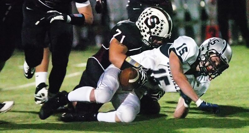 by: DAN BROOD - TACKLE TIME -- Sherwood senior Martin Layna (71) brings down Wilsonville's Derek Sunkle for a loss.