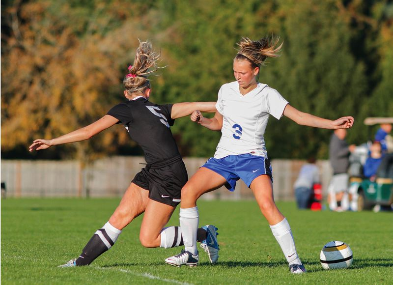 by: HILLSBORO TRIBUNE PHOTO: AMANDA MILES - Hillsboro freshman midfielder Kennedy Taube (3) battles for possession of the ball with McMinnville's McKenzie Davis during Monday's Pacific Conference girls soccer match.