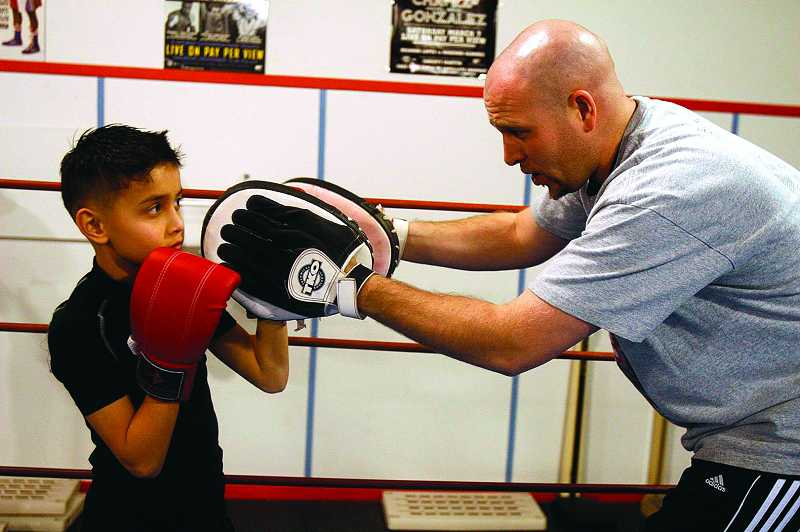 by: TIMES PHOTO: JONATHAN HOUSE - Boxing coach Jamie Huey helps Jake Amaya with his technique at Beaverton PAL's after-school boxing program. Amaya was getting in his last training session before the first fight of his career the next day.