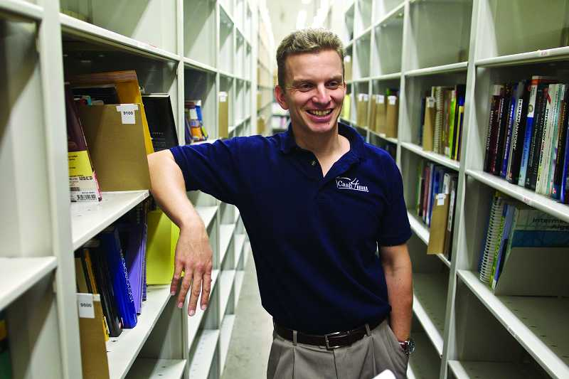 by: TIMES PHOTO: JAIME VALDEZ - Jim McKenzie Smith, president and chief executive officer of McKenzie Books and Cash4Books.net, shows off the shelves of used books ready for resale at his company's Cedar Hills warehouse.
