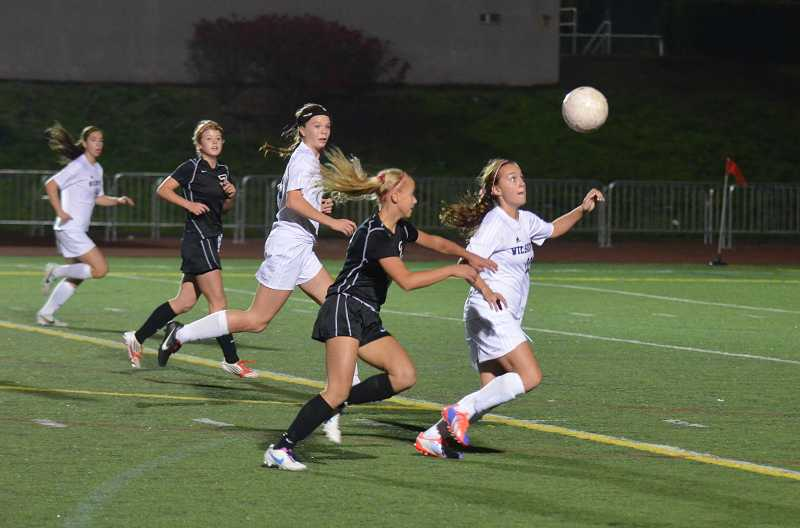 by: JEFF GOODMAN - Alexis Glavey (right) tracks a high-bouncing ball Oct. 17 at Randall Stadium. She and the Wilsonville girls soccer team earned their seventh-straight win with a shutout of top-ranked Sherwood.