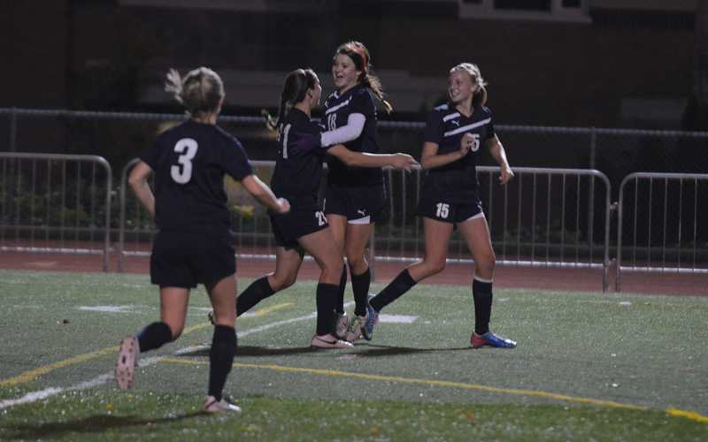 by: JEFF GOODMAN - Skylee Doman (second from left) hugs Chloe Bell, who scored with less than 2 minutes left to earn a 2-2 tie for the Canby girls soccer team Oct. 15 at West Linn.