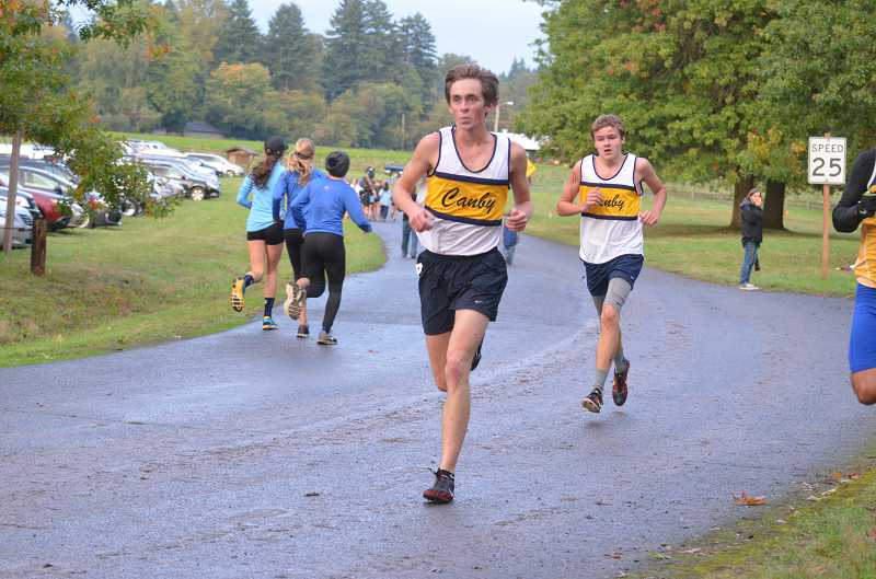 by: JEFF GOODMAN / FILE - Morgan Webber (front) leads the Canby boys cross-country team into its district meet Oct. 23 at Clackamas Community College. His father, Mark Webber, won a state title and carried the Cougars to fourth place in 1986.