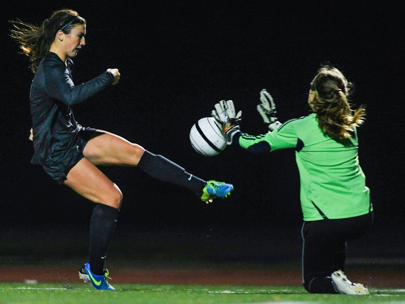 by: JOHN LARIVIERE - Oregon City goalkeeper Lizzy Coryell blocks a point blank shot by Clackamas forward Cassie Haehlen during last Thursdays game in Oregon City.