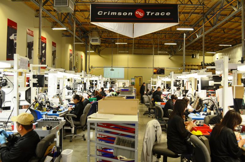 by: COURTESY OF CRIMSON TRACE - Crimson Trace production workers are shown at the company's Wilsonville factory.