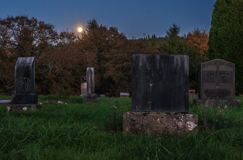 by: SPOKESMAN PHOTO: JOSH KULLA - These headstones at the Robert Bird Cemetery off Newland Road north of Wilsonville were photographed as Fridays full moon rose above the hills. They show significant damage from lichen, rain and other environmental degradation. This is one of the main challenges facing cemetery preservationists today.