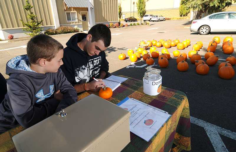 by: PAMPLIN MEDIA GROUP: VERN UYETAKE - Aaron Puppo, right, and his brother, Carson, look at their sales numbers from the pumpkin stand.