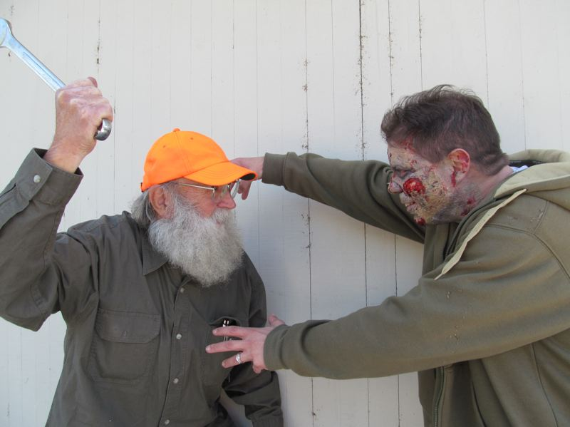 by: PHOTO BY ELLEN SPITALERI - Al Tate, left, finds out the hard way that a lug wrench is not effective against zombies, as personified by Sean Lavadour.