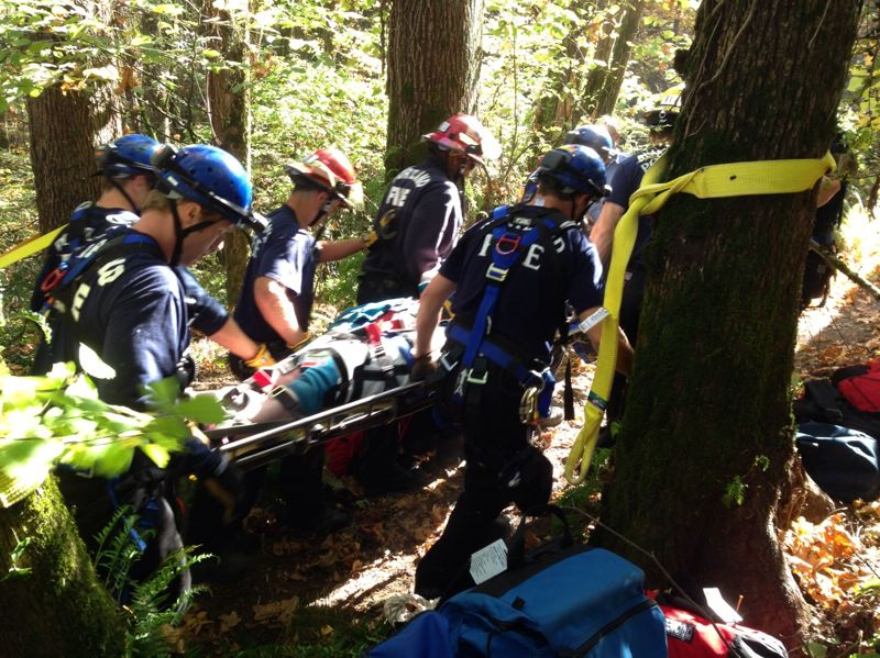 by: SUBMITTED PHOTO: RICH CHATMAN - The Portland Fire & Rescue Technical Team hauls a woman who fell over an embankment back to safety.