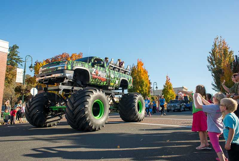 by: NEWS-TIMES PHOTO: CHASE ALLGOOD - A zombie monster truck spews candy with help from the crew perched above its undead monster tires.