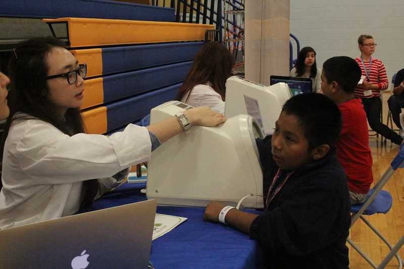 by: LINDSAY KEEFER - Sixth-grader Emanuel Lopez Lopez gets his blood pressure checked from one of many student volunteers, this one from Pacific University.