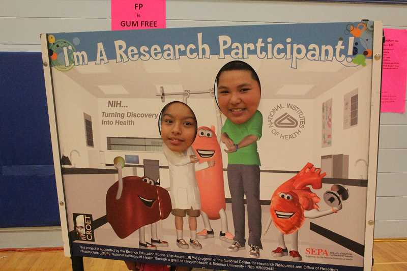 by: LINDSAY KEEFER - French Prairie sixth-graders Jennifer Cordero (left) and Jose Gonzalez Bravo pose with a cutout sign at the health fair Thursday.