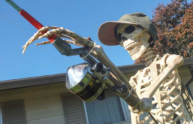 by: RAY HUGHEY - At one Aurora home, a skeletal angler wearing a fishing cap made his last cast at, of course, a fish skeleton.