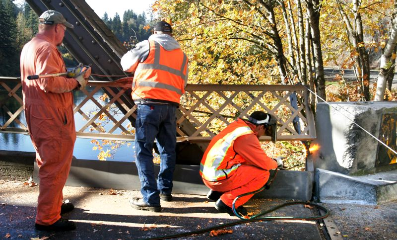by: OUTLOOK PHOTO: JIM CLARK - Multnomah County road maintenance workers attempt to repair the railing on the Stark Street Bridge after it was hit by a truck, closing the bridge. The bridge was reopened at about noon Monday.