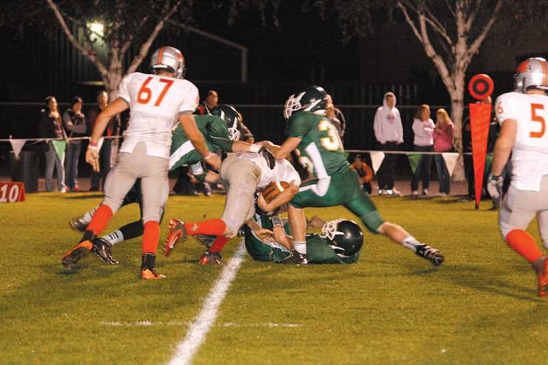 by: PHIL HAWKINS - A trio of North Marion defenders swarm Molalla quarterback Austin Alexander. The Huskies put pressure on Alexander throughout the game, pulling him down for five sacks while picking him off three separate times