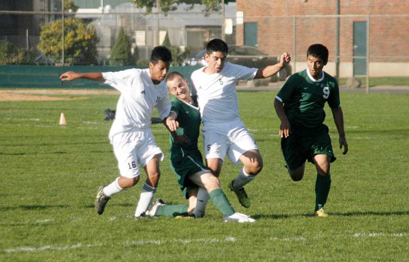 by: PHIL HAWKINS - North Marions Miguel Cano (left) and Aaron Caballero team up to fight past an Estacada defender in the Huskies 7-0 victory over the visiting Rangers on Oct. 15.