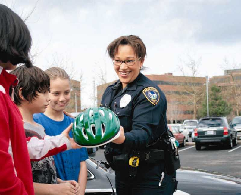 by: SUBMITTED PHOTO - Officer Kristan Rinell assists Metzger Elementary students. Rinell serves as a school resource officer in the Tigard-Tualatin School District, which recently agreed to contribute $50,000 to the security program in Tualatin.