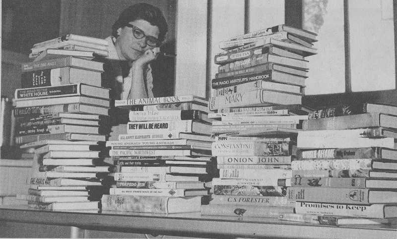 Tigard Librarian Ann Hicks looks over books for the newly opened Tigard Public Library from 1965. The library is celebrating its 50th anniversary with a party next weekend.