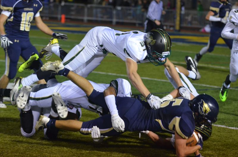 by: JEFF GOODMAN - West Linn's Brendan O'Brien gets airborn in an attempt to make a tackle during last week's loss to Canby. The Lions will close out the regular season on Friday against Lakeridge.