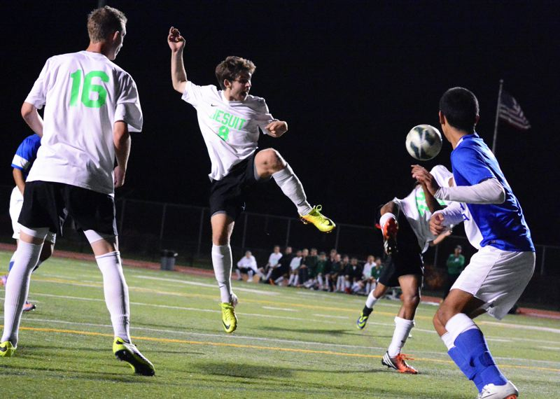 by: TIMES PHOTO: MATT SINGLEDECKER - Jesuit senior Henry Rocker high kicks a ball toward Aloha in the first half of the Crusaders 10-0 rout of the Warriors on Monday.