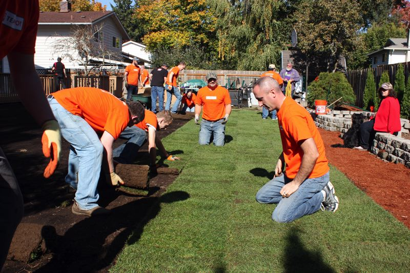 by: HILLSBORO TRIBUNE PHOTO: DOUG BURKHARDT - On Oct. 17, volunteers enjoy the sun as they tackle the Reynolds backyard, placing fresh sod and smoothing out the terrain at the Reynolds home on Northeast 18th Avenue.