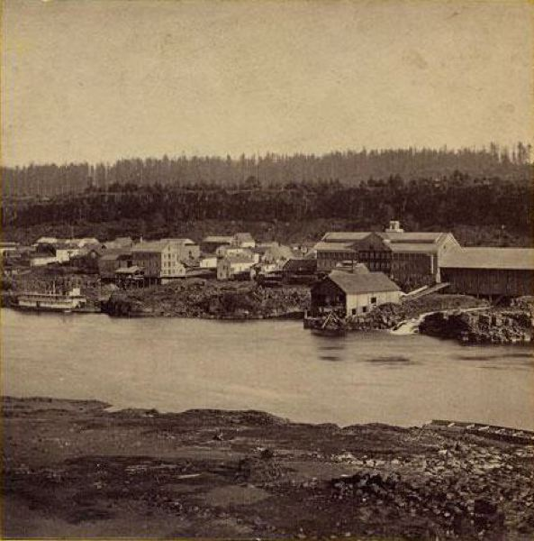 by: STEREOGRAPH BY CARLETON WATKINS - Oregon City just below the falls, showing flour mills and a sternwheel steamboat on the lower river in 1867 during the time of the Pioneer Paper Company. The Oregon City Flour Mill building is the one towards the left, four stories with the pitched roof, right above the boat moored along shore.