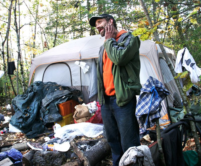 by: OUTLOOK PHOTO: JIM CLARK - Anthony, who has no permanent home, helps a friend clean out a campsite in Thousand Acres.