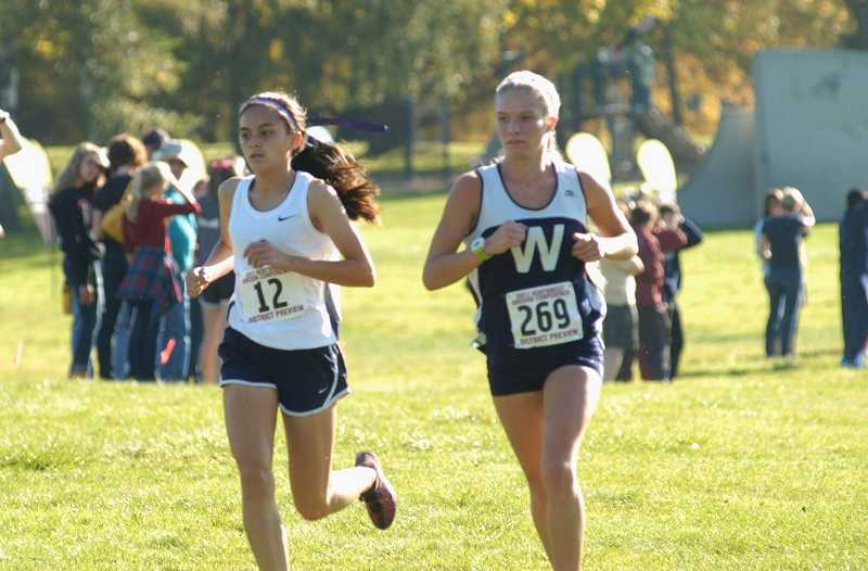 by: PARKER LEE / PAMPLIN MEDIA - Wilsonville senior Taryn Rawlings (left) and Liberty sophomore Rachel Khaw lead the field at the NWOC district meet Oct. 23 at Blue Lake Regional Park in Fairview. Rawlings won her third district title in four years.