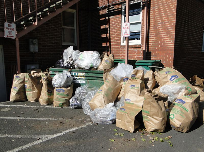 by: PHOTOS COURTESY: CITY OF MILWAUKIE - Several groups help pile the trash high after a cleanup of Milwaukie.