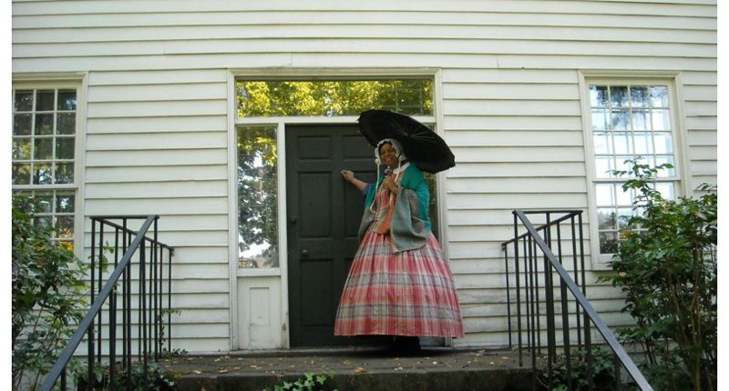 by: SUBMITTED PHOTO - Denyse McGriff, co-chair of the annual soiree, models her new period gown by the front door of the historic McLoughlin House in Oregon City.
