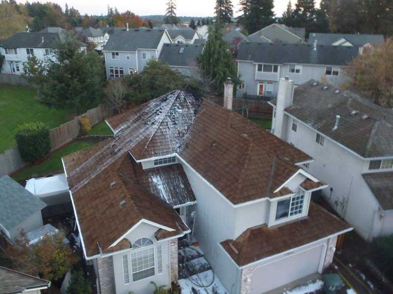 by: TVF&R - An aerial view of the house shows damage to the roof. The fire likely started after hot embers from an operating wood-burning stove landed on the house's cedar shake roof.